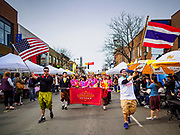 "29 APRIL 2017 - MINNEAPOLIS, MINNESOTA:  The opening parade, led by a man carrying the Thai flag, at Songkran Uptown. Several thousand people attended Songkran Uptown on Hennepin Ave in Minneapolis for the city's first celebration of Songkran, the traditional Thai New Year. Events included a Thai parade, a performance of the Ramakien (the Thai version of the Indian Ramayana), a ""Ladyboy"" (drag queen) show, and Thai street food.    PHOTO BY JACK KURTZ"