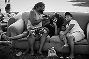 LIGNUM, VA -- 7/23/16 --  Mustafa Akbar sits on his daughter's lap. Ariel Monét Holmes, of Laurel, smiles as she speaks with her father, and her friend, Jenerra Burroughs, of Philadelphia, is at right.<br /> Mustock is a private music festival hosted by DC based musician, Mustafa Akbar. Now in it's 17th year, the event started as a fish-fry with Mustafa's mother when she was still living. Originally open to family and close friends, the event has grown steadily, and drew roughly 300 people over the weekend.…by André Chung #_AC14068