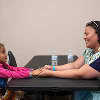 Alyssa Tia Little, 6, Navajo/Hopi holds hands with her auntie Elaine Owens backstage during a break in the Tiny Tot Pageant at El Morro Theatre, Monday, August 6, 2018.