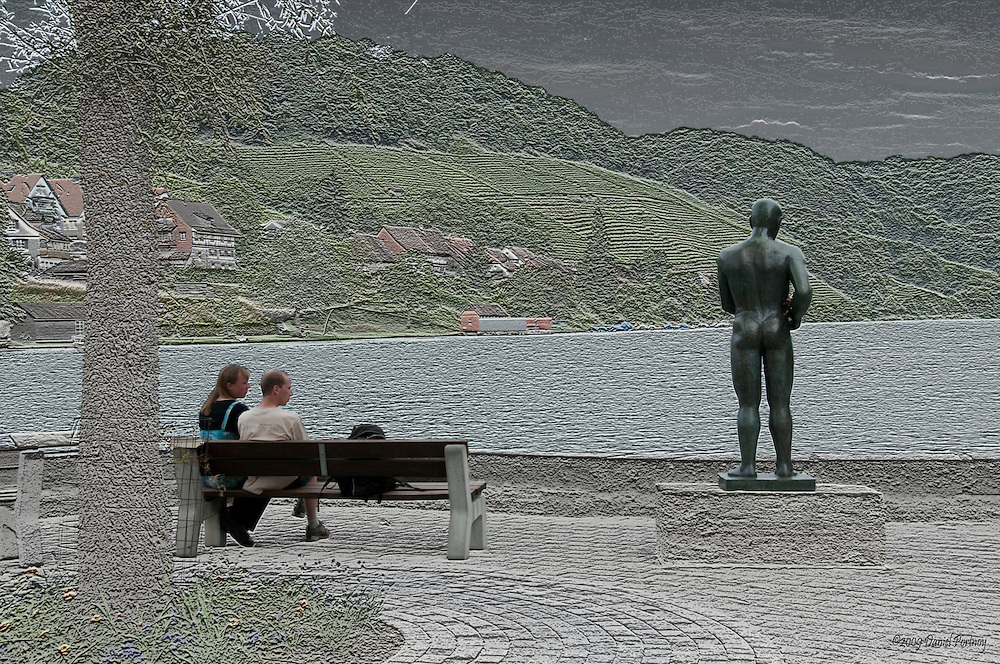 Statue and couple on bench at the river in Eglisau Switzerland