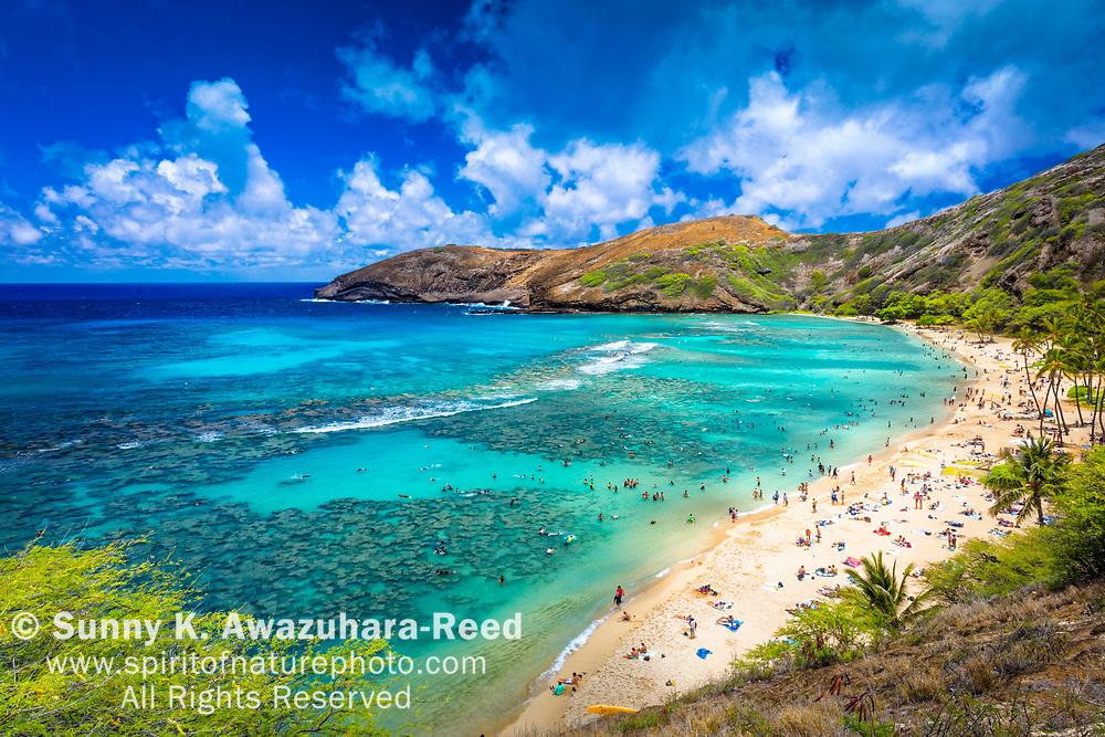 View of  Hanauma Bay with thousands of tourists under blue sky. Honolulu, Oahu Island, Hawaii.