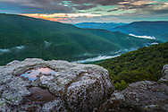 The colors of sunset can be seen reflecting off the pools of water after a fresh rain on top of Table Rock in Canaan Valley, West Virginia as fog rolls through the mountains.