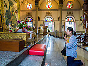15 FEBRUARY 2015 - BANGKOK, THAILAND:  A woman prays in front of a painting of the Virgin Mary after mass in Santa Cruz Catholic Church in the Kudeejeen neighborhood in Bangkok. Santa Cruz church was established in 1770  and is one of the oldest and most historic Catholic churches in Thailand. The church was originally built by Portuguese soldiers allied with King Taksin the Great. Taksin authorized the church as a thanks to the Portuguese who assisted the Siamese during the war with Burma. Most of the Catholics in the neighborhood trace their family roots to the original Portuguese soldiers who married Siamese (Thai) women. There are about 300,000 Catholics in Thailand in about 430 Catholic parishes and about 660 Catholic priests in Thailand. Thais are tolerant of other religions and although Thailand is officially Buddhist, Catholics are allowed to freely practice and people who convert to Catholicism are not discriminated against.     PHOTO BY JACK KURTZ