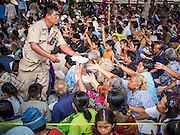 "09 AUGUST 2014 - BANGKOK, THAILAND:  People clamor for the last meal being handed out by volunteers at the Ruby Goddess Shrine in the Dusit section of Bangkok. The seventh month of the Chinese Lunar calendar is called ""Ghost Month"" during which ghosts and spirits, including those of the deceased ancestors, come out from the lower realm. It is common for Chinese people to make merit during the month by burning ""hell money"" and presenting food to the ghosts. At Chinese temples in Thailand, it is also customary to give food to the poorer people in the community.    PHOTO BY JACK KURTZ"