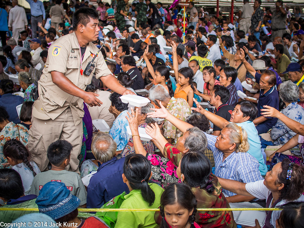 """09 AUGUST 2014 - BANGKOK, THAILAND:  People clamor for the last meal being handed out by volunteers at the Ruby Goddess Shrine in the Dusit section of Bangkok. The seventh month of the Chinese Lunar calendar is called """"Ghost Month"""" during which ghosts and spirits, including those of the deceased ancestors, come out from the lower realm. It is common for Chinese people to make merit during the month by burning """"hell money"""" and presenting food to the ghosts. At Chinese temples in Thailand, it is also customary to give food to the poorer people in the community.    PHOTO BY JACK KURTZ"""