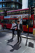 Two businessmen cross the road by a London bus during the 2018 heatwave in the City of London, the capital's historic financial district, on 2nd August 2018, in London, England.