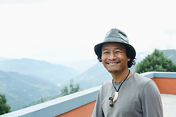 Portrait of a mid adult man on roof and smiling, Nepal