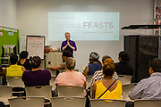 Jamaica, NY - 20 July 2017. Business plan presentations of the second cohort of the 12-week Jamaica FEASTS (Food Entrepreneurship and Training Space) program at the Queens Public Library. Entrepreneurship coach Michael Maldonado opening the final business plan presentations.