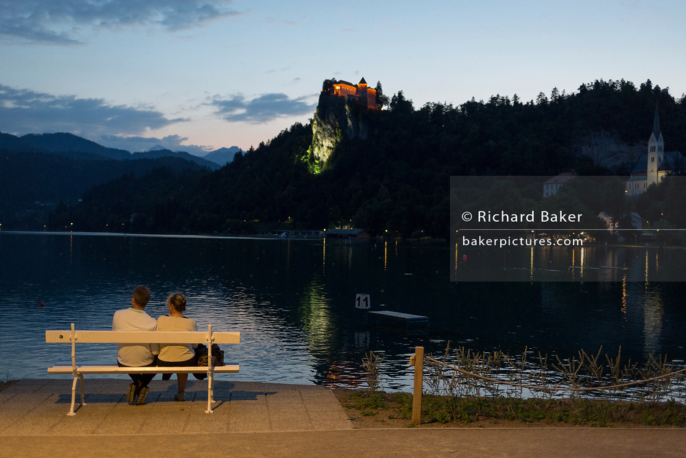 A couple sit on a bench overlooking Lake Bled and Bled castle on a summer evening, on 17th June 2018, in Bled, Slovenia.
