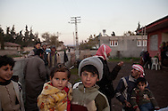 Mohanad holds his younger cousin Rimaz in the garden of their home in Davutpasa, a village bordering Syria. More than 60 members of the Jasem family share the three bedroom home in Davutpasa, Turkey. 12/29/2012. Bradley Secker for the Washington Post