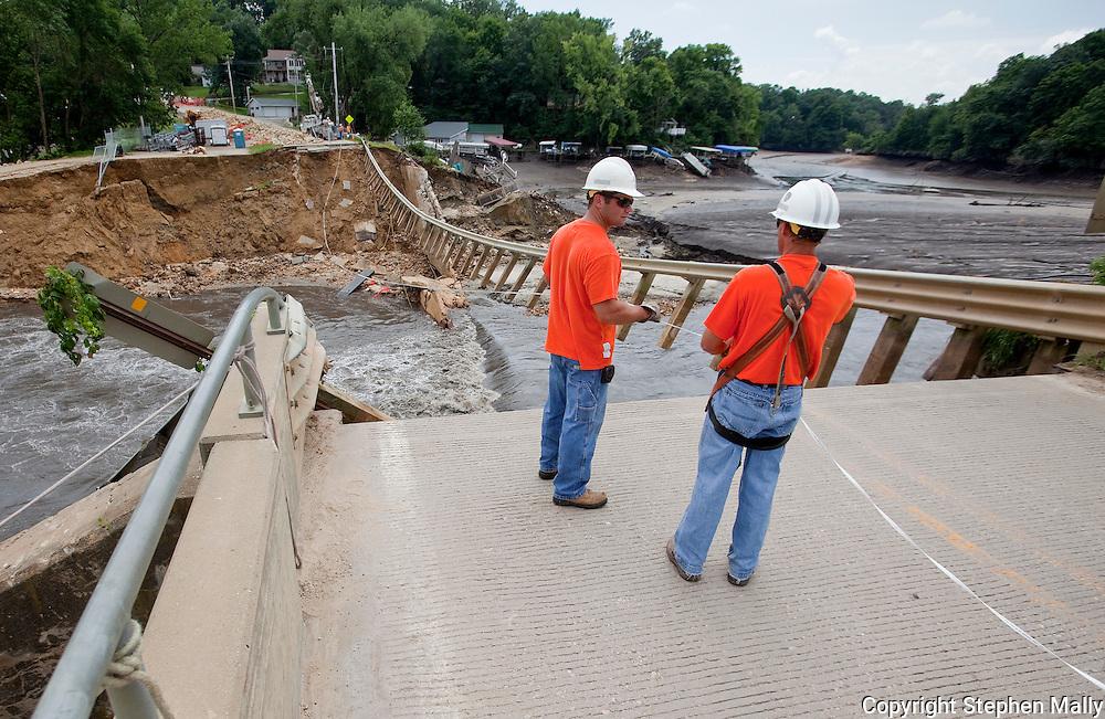 Workers prepare to run a new telephone line across the Delhi Lake Dam in Delhi, Iowa on Monday, July 26, 2010.