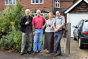 Peter Menzel and David Reed with Richard and Fenella Hodson in front of their house, Godalming, UK. (Material World Family from Great Britain UK) MODEL RELEASED..
