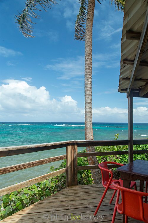 View outside a cafe with a table, chairs, sea and palm trees, Little Corn Island, Nicaragua