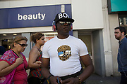 Man with a style of his very own including a BOY baseball cap on Oxford Street in London, England, United Kingdom.