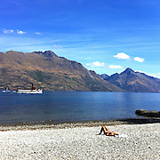 Sunbathers on the fore shore in Queenstown as the TSS Earnslaw, the 100 year old vintage coal fired passenger steam ship sails on Lake Wakatipu, Queenstown, New Zealand. The popular tourist attraction is celebrating it's centenary year with celebrations planned for October 2012.  Queenstown, Central Otago, New Zealand. 29th February 2012. Photo Tim Clayton