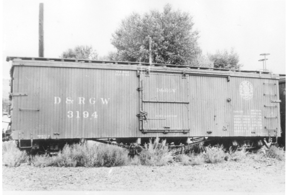 """Side view of box car #3194 at Durango.<br /> D&RGW  Durango, CO  Taken by Best, Gerald M. - 8/5/1940<br /> In book """"Narrow Gauge Pictorial, Vol. III: Gondolas, Boxcars and Flatcars of the D&RGW"""" page 117<br /> See original photo RD054-060."""