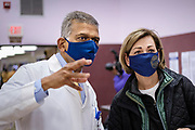 27 MARCH 2021 - DES MOINES, IOWA: Dr. YOGESH SHAH, Chief Medical Officer and Vice President of Medical Affairs at Broadlawns Medical Center, talks to Iowa Governor KIM REYNOLDS during a COVID-19 (Coronavirus) vaccination clinic at Corinthian Baptist Church in Des Moines, Saturday. The clinic was organized by Broadlawns Medical Center and the United Way and provided more than 1,100 shots to Des Moines area residents. The clinic was a part of an effort to reach communities of color in Iowa, who are vaccinated at rates below the state average.      PHOTO BY JACK KURTZ