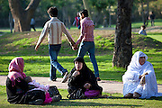 Men holding hands and muslim women with child in gardens at Humayuns Tomb, in New Delhi, India
