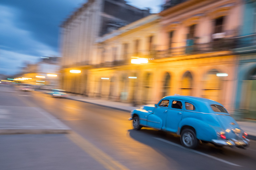 Classic car in motion at dusk in Havana, Cuba.
