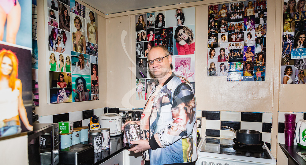 Shaun Smith, 52, from Basildon in Essex makes a cup of tea in his kitchen which, like the rest of his home has every wall plastered with pictures of Cheryl Cole. He has built up a huge collection of Cheryl Cole memorabilia in the space of about eight months after she impressed him in a music video he was watching.. PLACE, January 24 2019.
