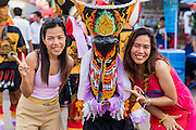 27 JUNE 2014 - DAN SAI, LOEI, THAILAND:  Tourists pose for photos with a ghost at the Ghost Festival. Phi Ta Khon (also spelled Pee Ta Khon) is the Ghost Festival in Dan Sai. Over three days, the town's residents invite protection from Phra U-pakut, the spirit that lives in the Mun River, which runs through Dan Sai. People in the town and surrounding villages wear costumes made of patchwork and ornate masks and are thought be ghosts who were awoken from the dead when Vessantra Jataka (one of the Buddhas) came out of the forest.   PHOTO BY JACK KURTZ