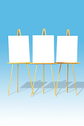 Three blank white easels