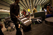 A family just arrived from Chennai (India) drags heavy suitcases from the carousel in the arrivals of Heathrow Airport's T5