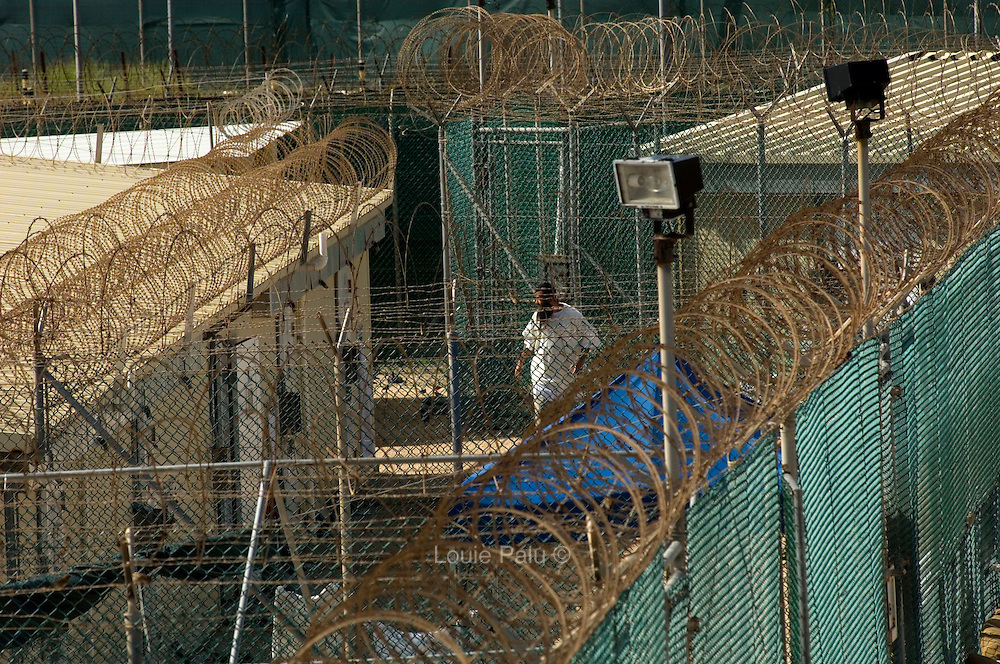 """A detainee seen through a maze of fence and wire in Camp 4 at the detention facility in Guantanamo Bay, Cuba. Camp 4 is a communal style camp where more compliant detainees live in small groups and have access to a more open air environment. Approximately 250 """"unlawful enemy combatants"""" captured since the September 11, attacks on the United States continue to be held at the detention facility.(Image reviewed by military official prior to transmission)"""