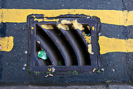 Maintenance Hole- and Drain Covers of Wirral by Colin McPherson, 2020-21.<br /> <br /> A gully cover manufactured by Deptford Foundry, south-east London, metal foundry formed in 1831 by engineer Josiah Stone. The original foundry on Arklow Road was once a thriving centre of design excellence, producing a variety of metal goods from propellers, to manhole covers and train parts. The site is now an upmarket housing development.