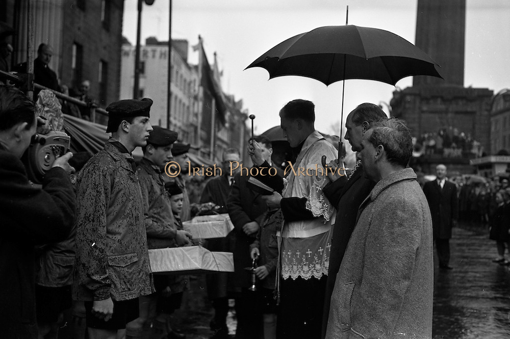 17/03/1963<br /> 03/17/1963<br /> 17 March 1963<br /> Shamrock is blessed before the N.A.I.D.A. annual St. Patrick's Day Industrial Parade, outside the G.P.O. on O'Connell Street Dublin. To the right of the priest are Minister for Industry and Commerce, Jack Lynch (umbrella) and Aodhagan Brioscu,  President of the N.A.I.D.A..