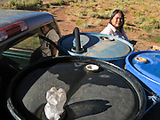 22 OCTOBER 2007 -- MONUMENT VALLEY, UT: MARIE CLY, a Navajo Indian living on the Navajo Reservation in northern Arizona, pulls the hose out of barrels after filling 50 gallon barrels with potable water at the well at Goulding's Trading Post near Monument Valley, UT. The well at Goulding's was first dug by Seventh Day Adventists missionaries and is the only source of clean, free water for miles around. More than 30 percent of the homes on the Navajo Nation, about the size of West Virginia and the largest Indian reservation in the US, don't have indoor plumbing or a regular supply of domestic water. Many of these homes have to either buy water from commercial vendors or haul water from public wells. A Federal study showed that the total cost of hauling water was about $113 per 1,000 gallons. A Phoenix household, in comparison, pays just $5 a month for up to 7,400 gallons of water. The lack of water on the reservation means the Navajo are among the most miserly users of water in the United States. Families that have to buy or haul water use only about 15 gallons of water per day per person. In Phoenix, by comparison, the average water use is about 170 gallons per day.  Photo by Jack Kurtz