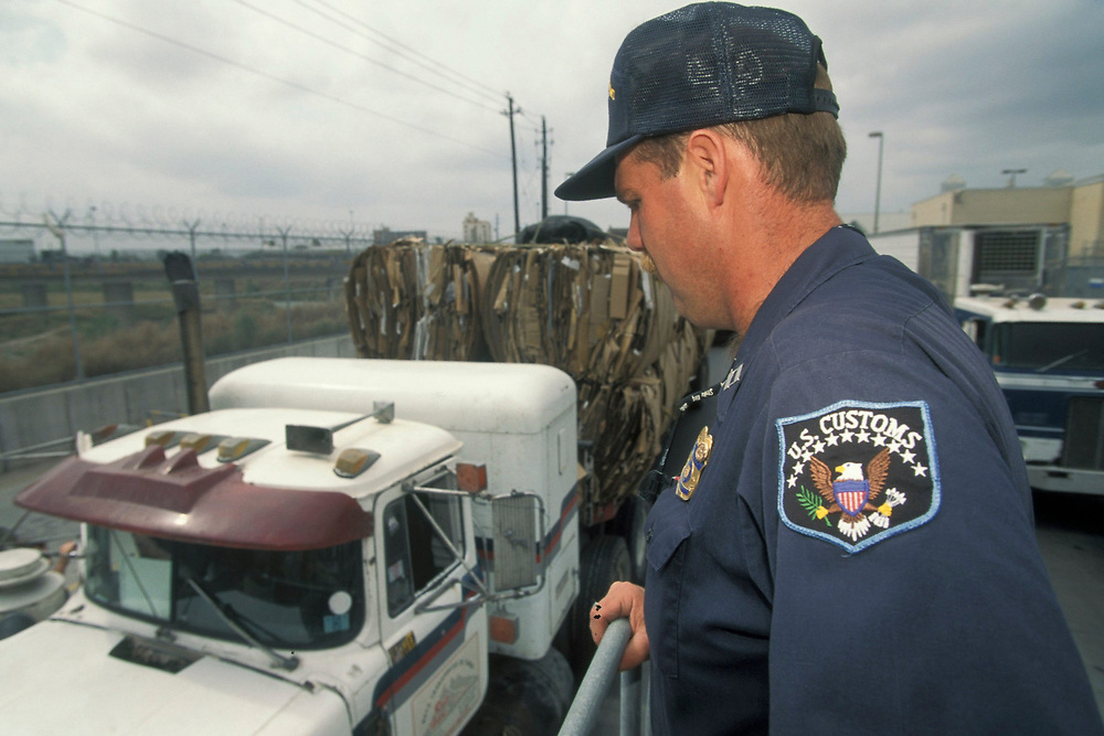 Anglo male US Customs Agent searching trucks crossing US-Mexico border for contraband.<br /> ©Bob Daemmrich