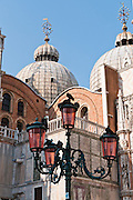 """The Byzantine architecture of Saint Mark's Basilica (Basilica Cattedrale Patriarcale di San Marco) dates from 1063 AD. Saint Mark's Basilica is the cathedral church of the Roman Catholic Archdiocese of Venice. Piazza San Marco (Saint Mark's Square) is the prime walking center of Venice. The Piazzetta extends Piazza San Marco to the Venetian Lagoon waterfront. The Doge's Palace (right), built in gothic style 1309-1424 AD, housed the elected leader and government of the Republic of Venice, until Napoleon occupied in 1797. Venice (Venezia) is the capital of Italy's Veneto region, named for the ancient Veneti people from the 10th century BC. The romantic """"City of Canals"""" stretches across 117 small islands in the marshy Venetian Lagoon along the Adriatic Sea in northeast Italy. The Republic of Venice wielded major sea power during the Middle Ages, Crusades, and Renaissance. Riches from Venice's silk, grain, and spice trade in the 1200s to 1600s built elaborate architecture combining Gothic, Byzantine, and Arab styles. Venice and the Venetian Lagoon are honored on UNESCO's World Heritage List."""
