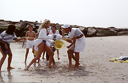 friends at the beach playing a game of limbo