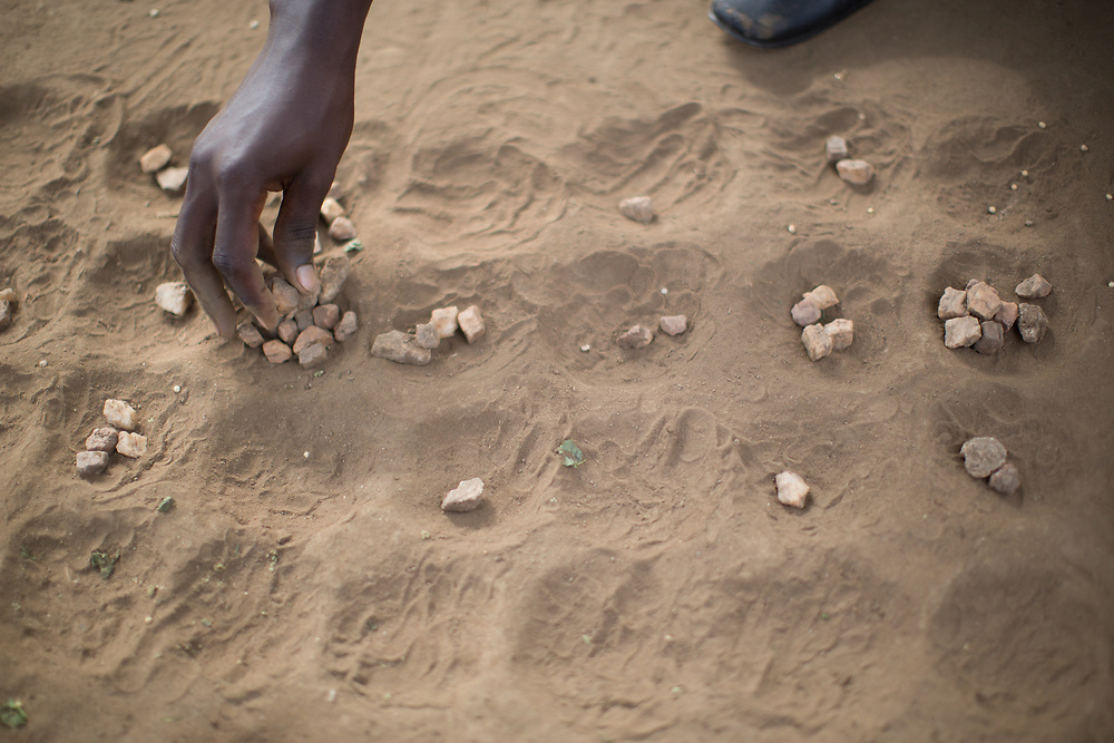 The game of Bao is played across Africa. Here in the Bidibidi Refugee Settlement is is played with stones in a board in the ground.