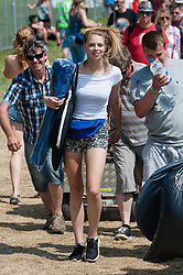© Licensed to London News Pictures. 11/06/2015. Newport, UK.  Festival goers arrive at Isle of Wight Festival 2015 carrying their tents and suppliers. Today has been hot and sunny.  This years festival include headline artists the Prodigy, Blur and Fleetwood Mac.  Photo credit : Richard Isaac/LNP
