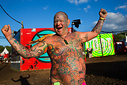 Mad Al, covered in tattoos in the Shangri La field, Glastonbury Festival 2016. The Glastonbury Festival is the largest greenfield festival in the world, and is now attended by around 175,000 people. Its a five-day music festival that takes place near Pilton, Somerset, United Kingdom. In addition to contemporary music, the festival hosts dance, comedy, theatre, circus, cabaret, and other arts. Held at Worthy Farm in Pilton, leading pop and rock artists have headlined, alongside thousands of others appearing on smaller stages and performance areas.