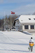 A male snowboarder walking at Milzkalns ski resort on 12th February 2019 in Milzkalns in Latvia. The small ski resort of Milzkalns is located in the Engure Municipality in western Latvia.