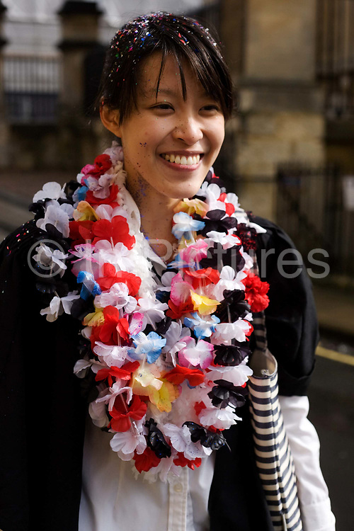A female student from Singapore celebrates her end of Chemistry Finals (exams)  at Trinity College, Oxford. With glitter sticking to her dark hair, this talented international Asian student smiles with great relief and intends to celebrate the end of her examinations at Oxford by partying with friends. In celebration of this achievement, of surviving the pressure and stress of the last examinations, students all over the city in the same fortunate position, often carry bottles of alcohol to their residences where the partying continues, shared by contemporaries and friends. In the street, the young lady from Singapore pauses before walking along Catte Street, past the Bodleian Library. Oxford is the third oldest surviving university in the world and the oldest surviving in the English-speaking world. Foreigners make up one third of the student body.