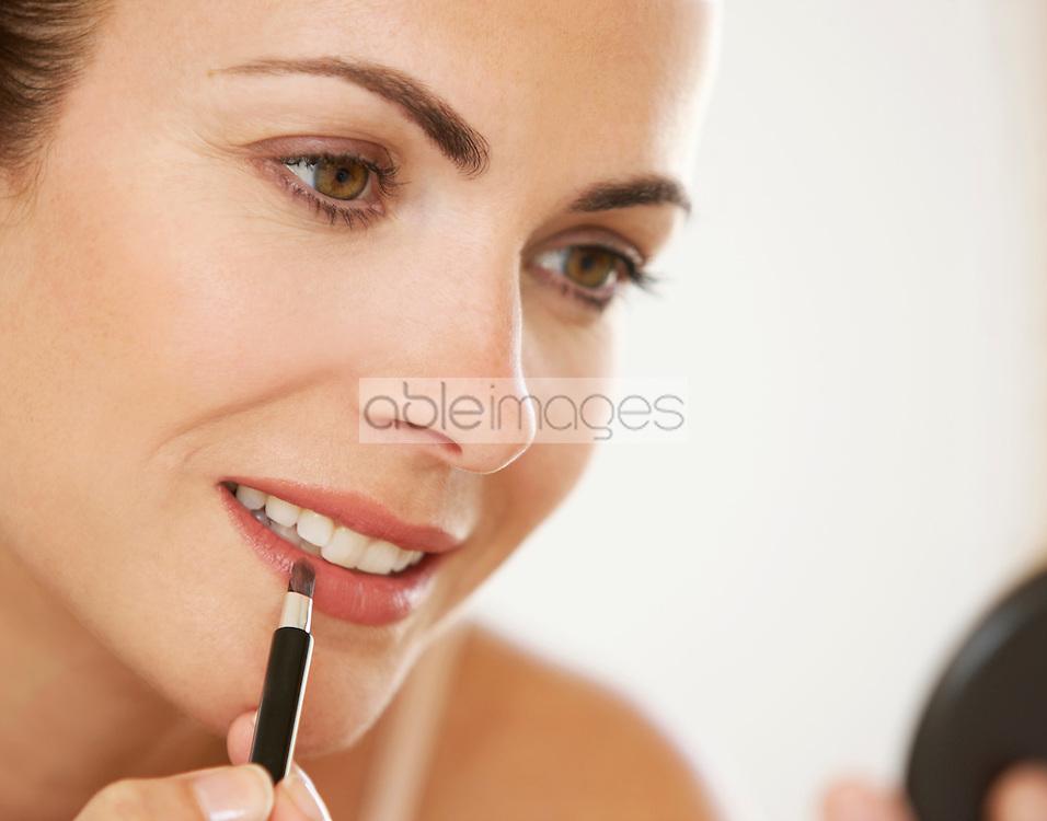 Woman Using Lipstick Brush, Close-up view