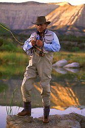 Stock photo of a fisherman tying a fly to his leader beside a calm lake in a remote mountainous area of Colorado.