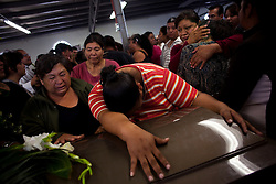 Family members grieve during the funeral for a group of teenagers who were killed during a massacre at a birthday party in Ciudad Juarez.