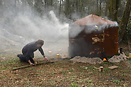 A charcoal kiln being lit in deciduous woodland in southern England