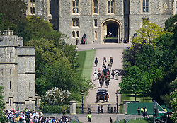 © Licensed to London News Pictures. 17/05/2018. Windsor, UK. A crowd watches as a covered coach and horses approach Windsor Castle during a rehearsal of the wedding day  procession of Prince Harry and Meghan Markle. Photo credit: Peter Macdiarmid/LNP