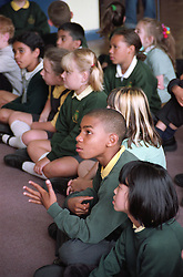 Primary school pupils sitting on floor in school hall during assembly,
