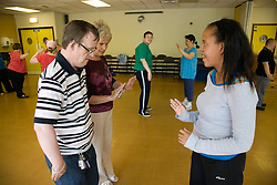 Day Service Officer showing service users with learning disabilities a dance movement,