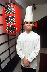 Portrait of male chef wearing chef's hat and overalls standing in Japanese restaurant,
