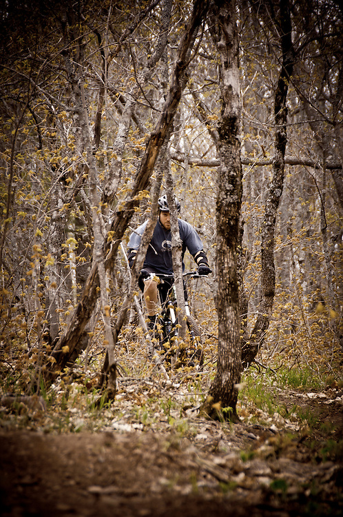A mountain biker rides through trees along the Flow single track trail on Brockway Mountain in Copper Harbor Michigan.