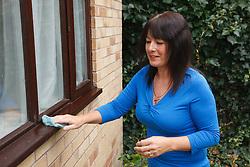 White woman washing window frame