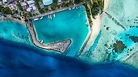 Aerial view of local, inhabited island Felidhoo, located in Vaavu Atoll, Maldives, Indian Ocean with boats / dhonis anchored in the harbour and local beach